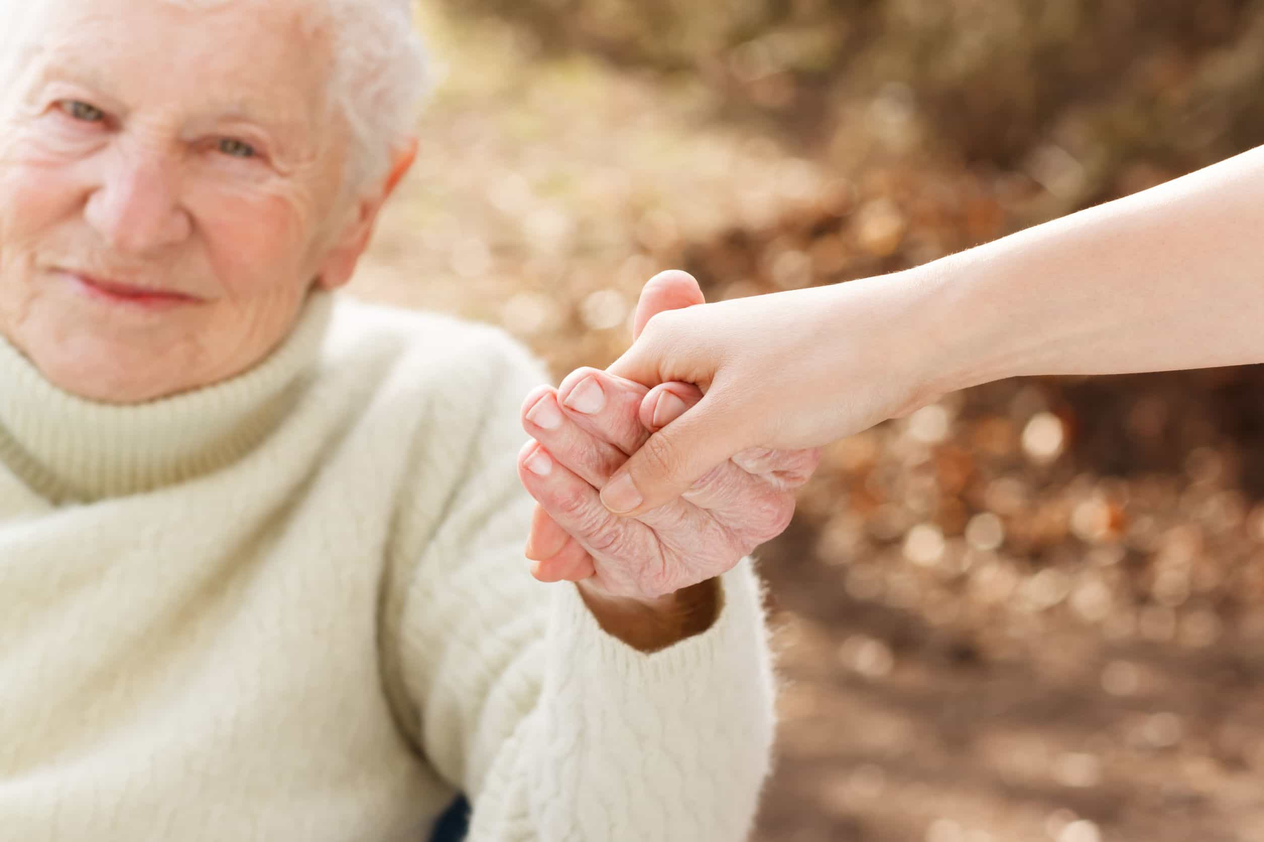31072401 - elderly woman holding hands with young woman outside