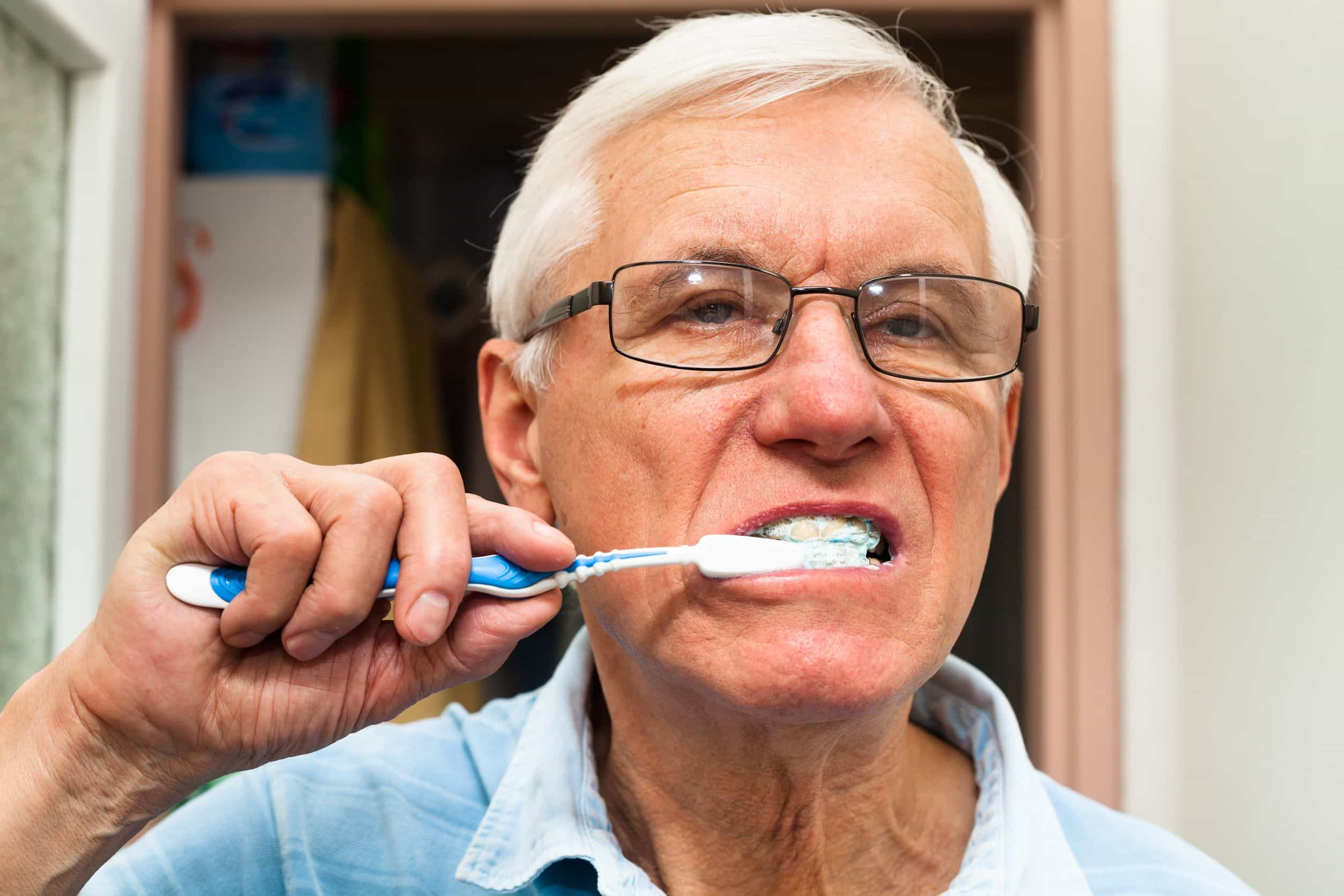 17546756 - close up of senior man brushing his teeth.
