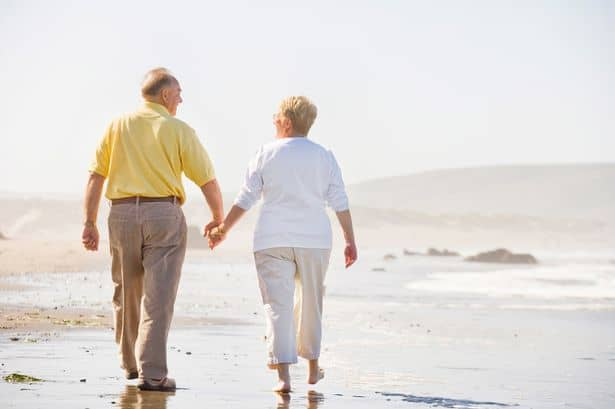 Mature couple walk on beach